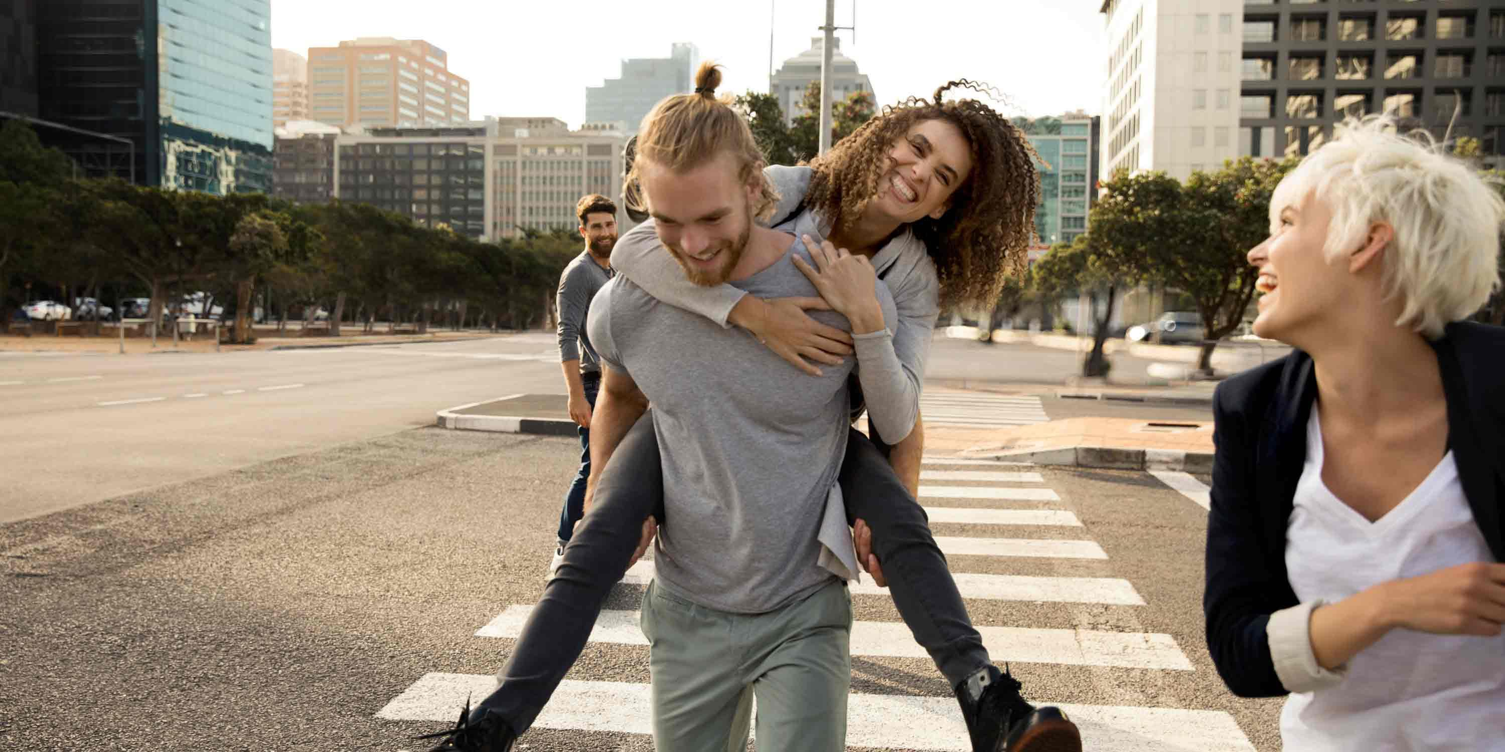 man-carrying-woman-crossing-street